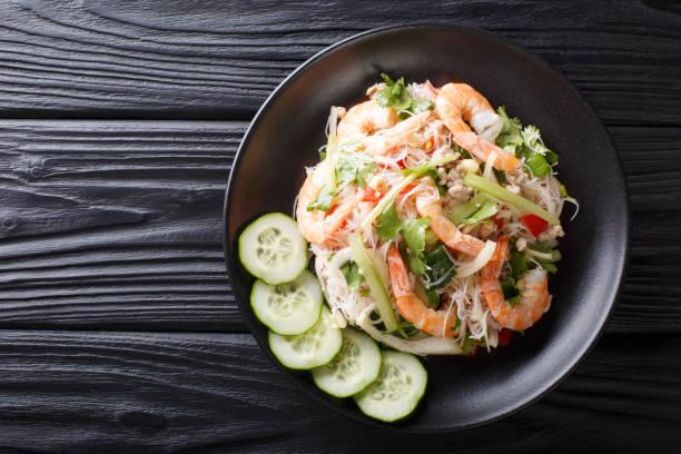 würziger yum woon sen salat mit garnelen, schweinefleisch und gemüse aus nächster nähe auf dem tisch. horizontale obere ansicht - erdnusssalatdressings stock-fotos und bilder
