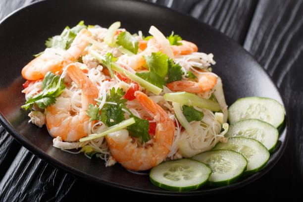 würziger yum woon sen salat mit garnelen, schweinefleisch und gemüse aus nächster nähe auf dem tisch. horizontal - erdnusssalatdressings stock-fotos und bilder