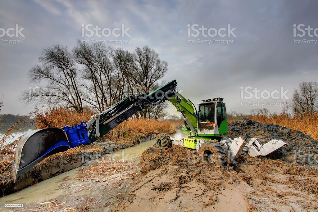 spider excavator dig inflow into lake for a fish pass stock photo