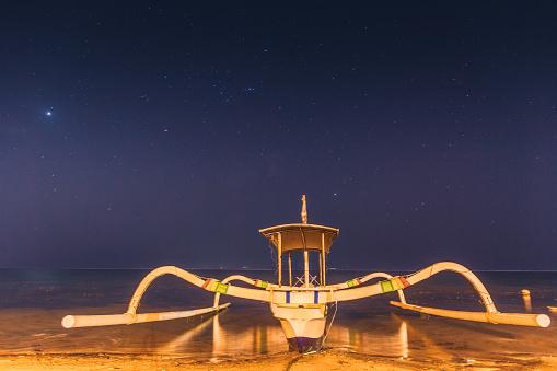 Spider gondola boat at tropical beach sea in Bali indonesia at night