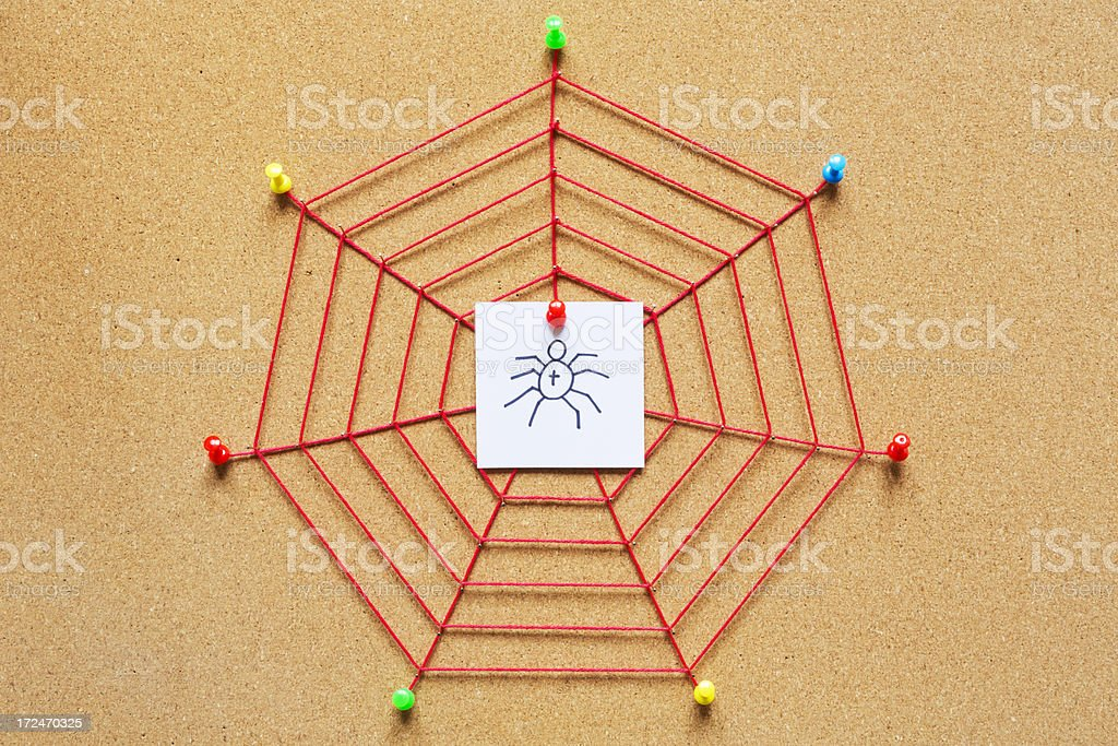 Spider web on a cork bulletin board royalty-free stock photo