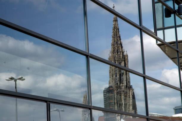 Spiegelung Ulmer Münster Der Turm des Ulmer Münsters spiegelt sich in der Glasfassade eines Gebäudes ulm minster stock pictures, royalty-free photos & images