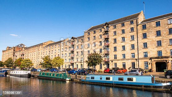 Narrowboats and cars outside the historic buildings at Spiers Wharf near Cowcaddens in Glasgow on a sunny day.