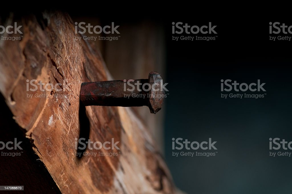 Spike Driven into Wooden Cross stock photo