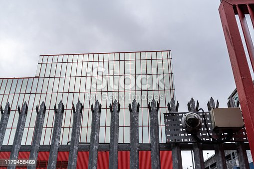 Galvanised spiked fence, security camera and office building exterior.  Constructed in 1972, the building's facade was designed by McNeill-McManus & Albann-McKinney.  Belfast, Northern Ireland.