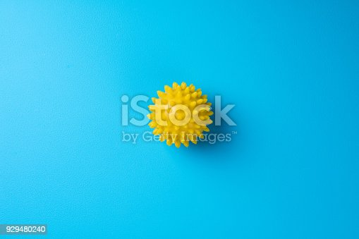 istock Spiky massage ball on blue background top view. Self massage, healthy, wellness and reflexology therapy concept 929480240