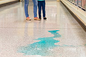 Spill hazard in supermarket with the legs of shoppers in the background.  A health and safety slips and trips topic.