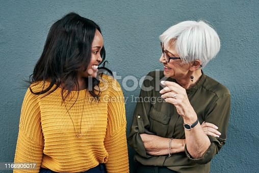 Shot of two cheerful businesswomen having a discussion while standing against a wall outdoors