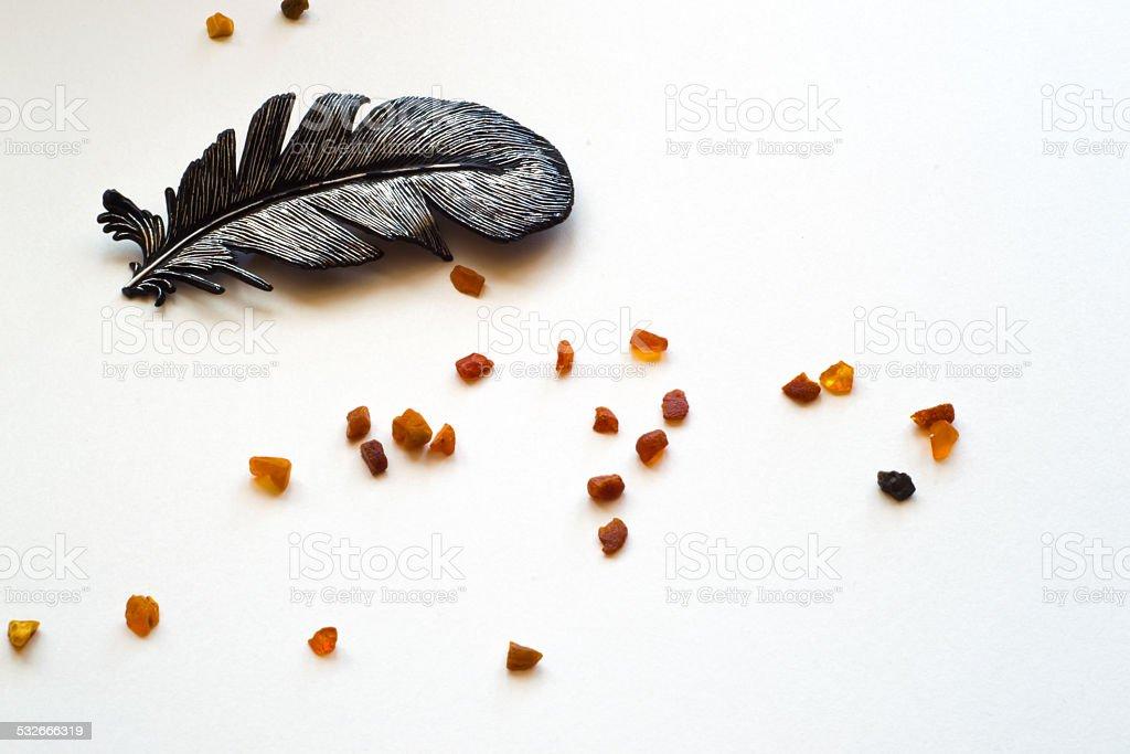 Spilled amber und Feder auf weißem Hintergrund – Foto