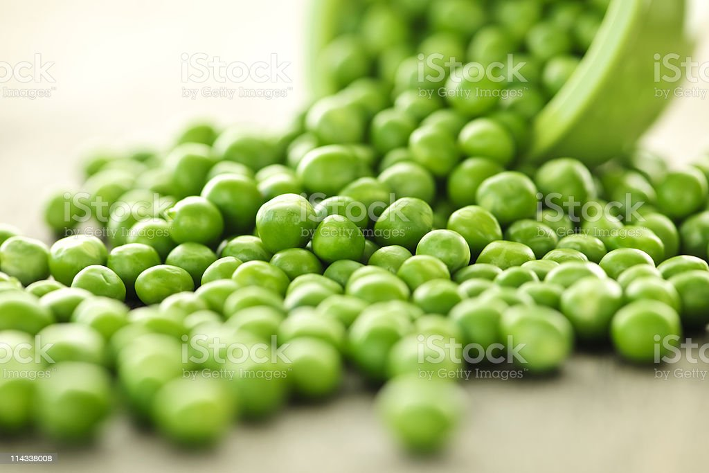 Spilled bowl of green peas stock photo