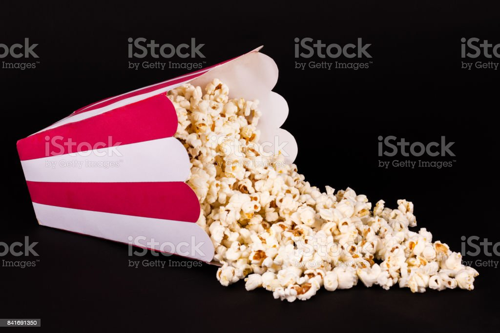Spilled box of popcorn on black background stock photo