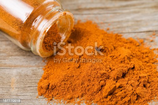 Cayenne pepper spilled out of a jar onto a weathered wooden surface.