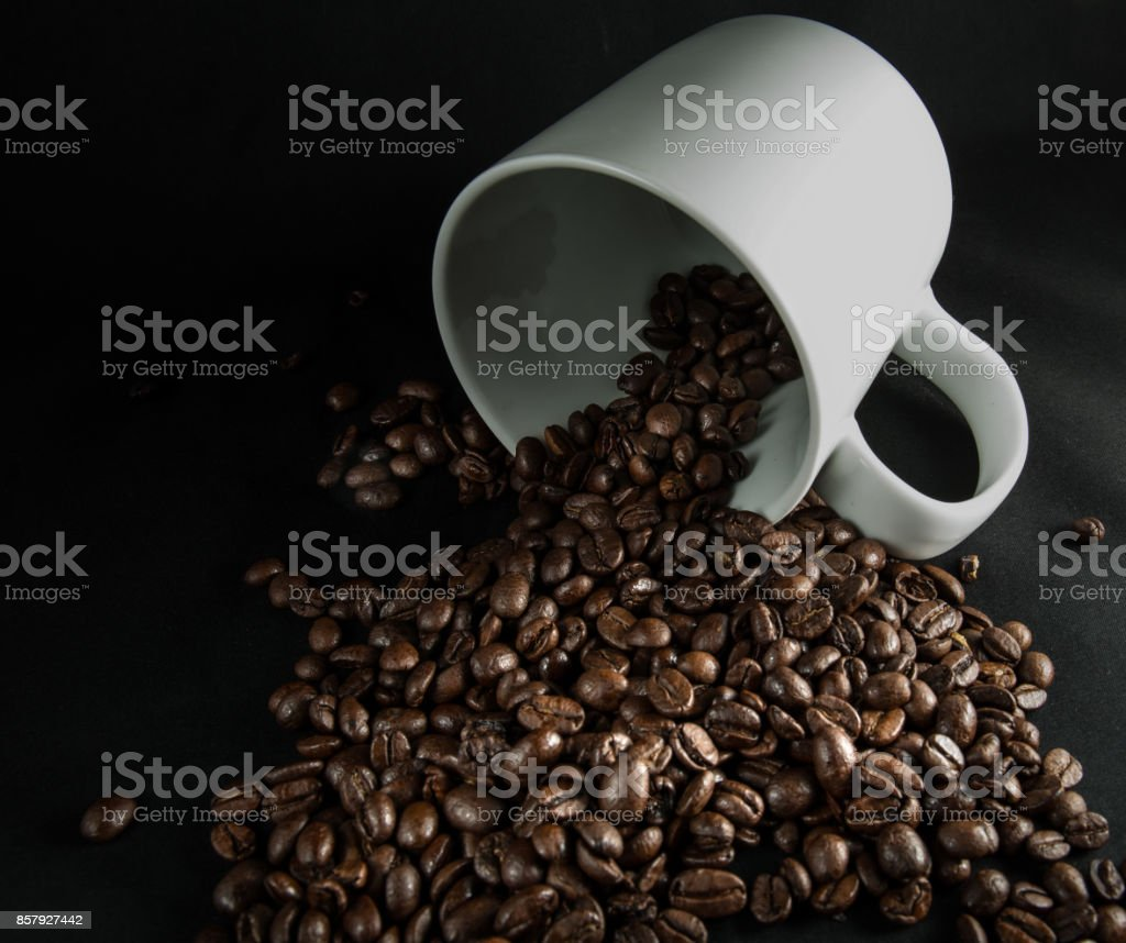 Spilled coffee beans from a mug stock photo