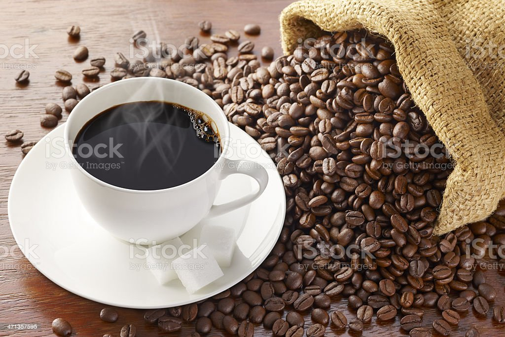 Spilled coffee beans surround saucer with coffee and sugar stock photo