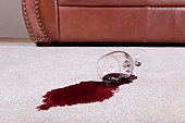 A wine glass with a red wine spill creating a puddle rests on a tan loop pile carpet.  The wine glass rests on the spilled wine.  The glass has a long stem and wide base.  The spill fans out from the top of the glass.  The spill appears deeper underneath the glass and then becomes a little lighter as it fans out.  The spill is oval in shape.  A tan leather couch with decorative metal buttons that run up the side sits in the background.  Neutral colored walls are also in the background.