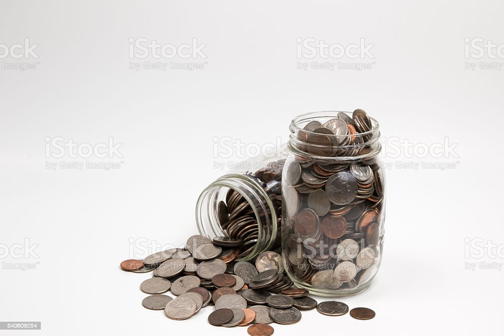 Spilled jars of coins stock photo