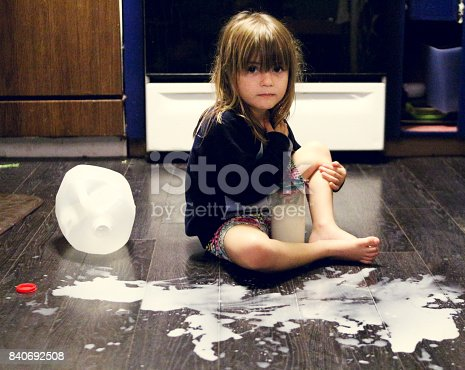 Little girl sits by the milk she spilled all over the floor