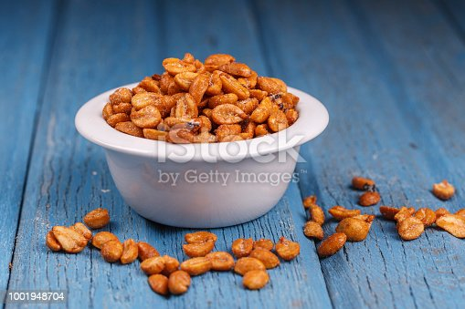 A studio image of roasted peanuts in a dish with some spilling over.