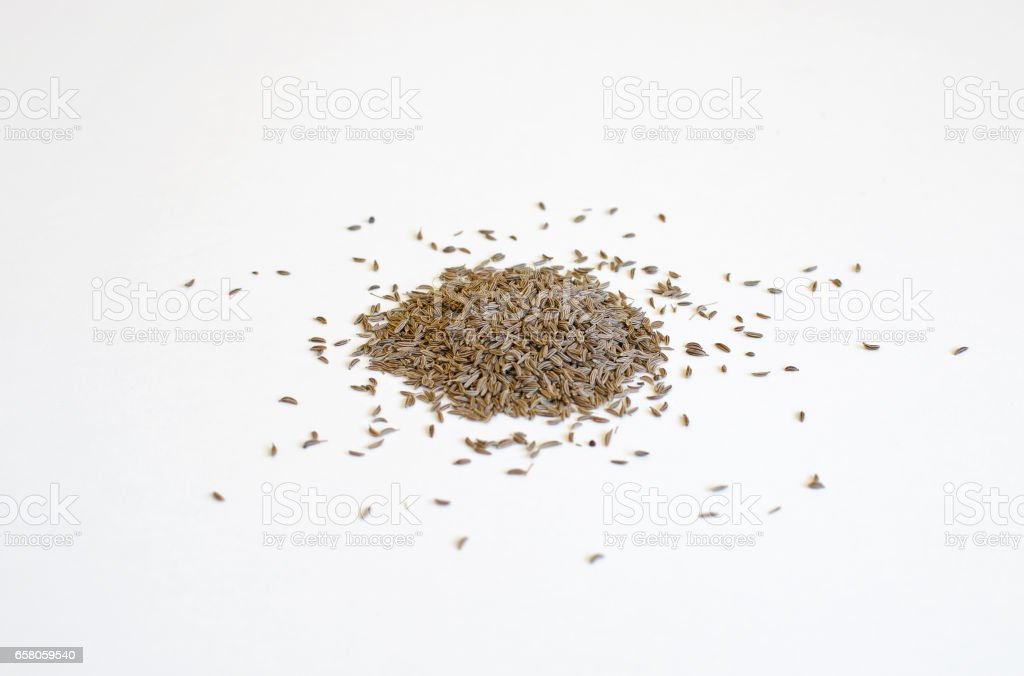 Spilled pile of cumin seeds are isolated on a white background stock photo