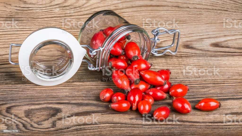 Spilled red fruits of wild rose on wooden table stock photo