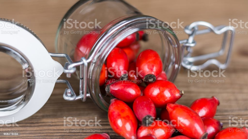 Spilled red rosehips on wood background stock photo