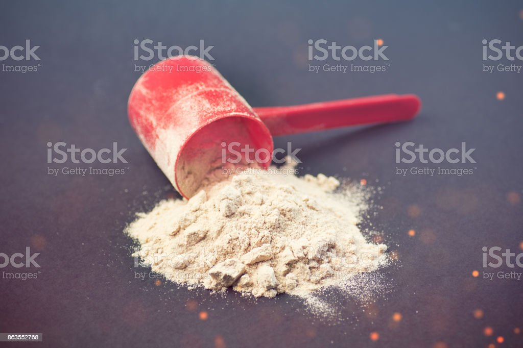 spilled scoop of protein powder stock photo