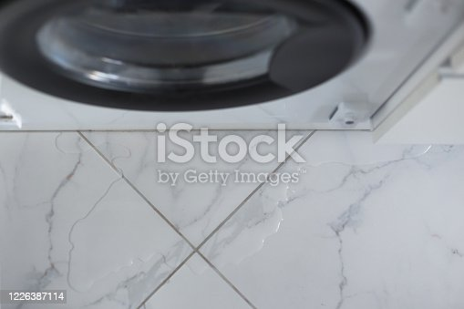 487597124 istock photo Spilled water leaked from washing machine built into the kitchen furniture. Spilled water on the tiled floor, flooding. 1226387114