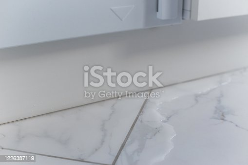 487597124 istock photo Spilled water leaked from washing machine built into the kitchen furniture. Spilled water on the tiled floor, flooding. 1226387119