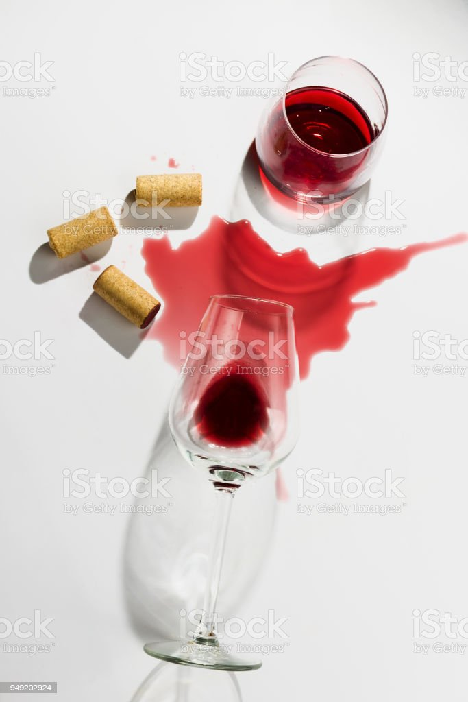 spilled wine glasses and wooden wine cords on white background