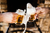 Close up of unrecognizable men spilling beer while toasting with it.