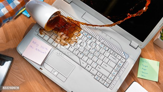 Cup of coffee spilling on white laptop in office desk.