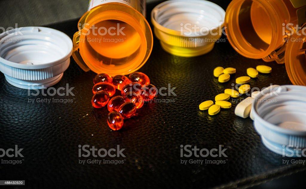 Derramar pastillas fármacos abrir frascos en cuero negro - foto de stock