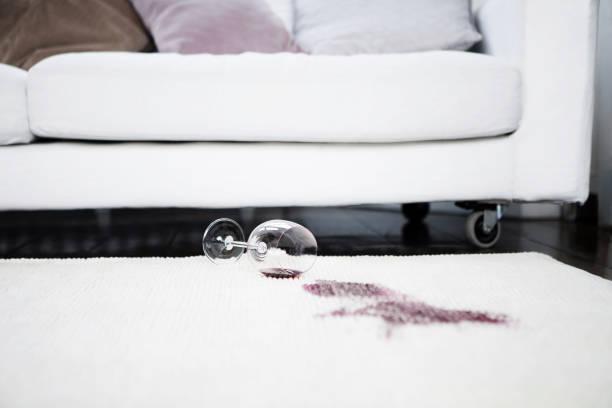 Spilt red wine on rug stock photo