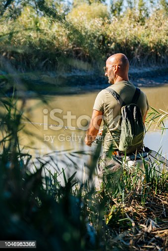 139888169istockphoto Spin fishing on a river with rod 1046983366