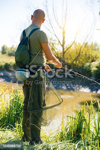 139888169istockphoto Spin fishing on a river with rod 1046986704