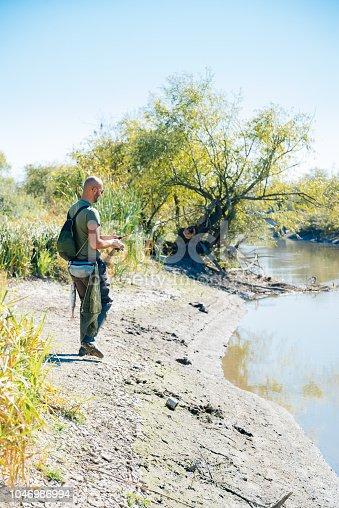 139888169istockphoto Spin fishing on a river with rod 1046986994