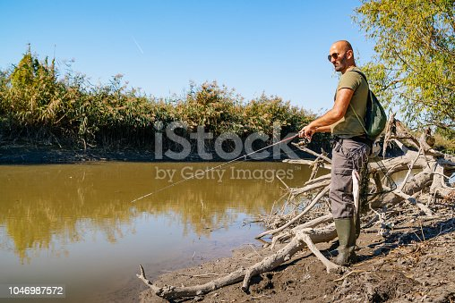 istock Spin fishing on a river with rod 1046987572