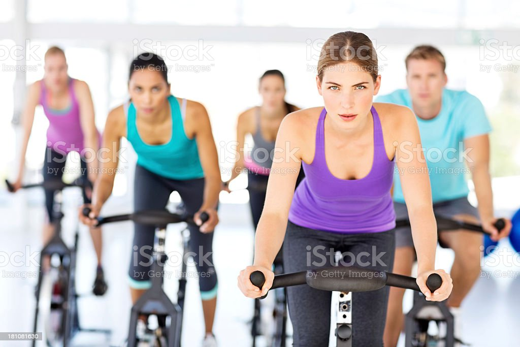 Spin Instructor And Class Exercising On Bikes In Health Club royalty-free stock photo