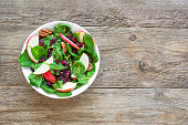 Spinach, apple salad with  pecan nuts and dry cranberries on wooden background, copy space. Heathy clean vegan raw food, fresh salad.