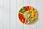 close-up of Spinach Artichoke leafy cheese Dip set with Tortilla Chips, cucumber, celery sticks, tomato slices and red bell pepper, horizontal view from above, flat lay, free space
