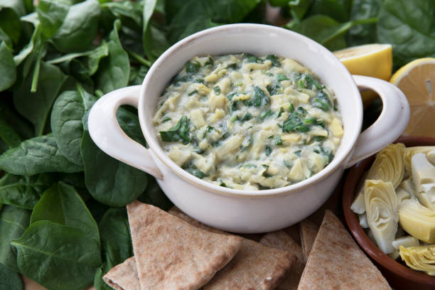 Spinach Artichoke Dip with Fresh Ingredients Bowl of vegan spinach artichoke dip with pita and ingredients. dipping sauce stock pictures, royalty-free photos & images