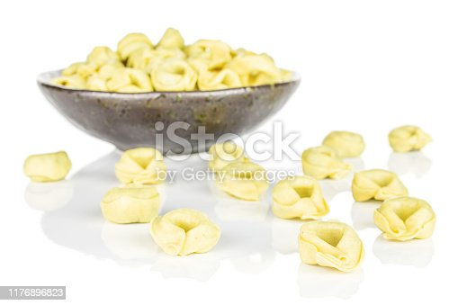 Lot of whole fresh yellow spinach filled tortelloni in dark ceramic bowl isolated on white background
