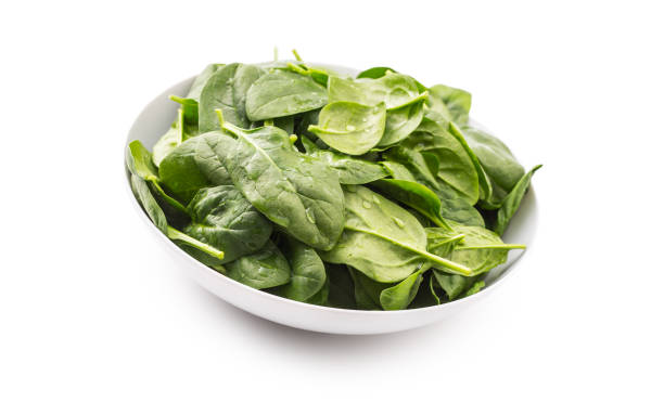 Spinach. Fresh baby spinach leaves in plate isolated on white stock photo