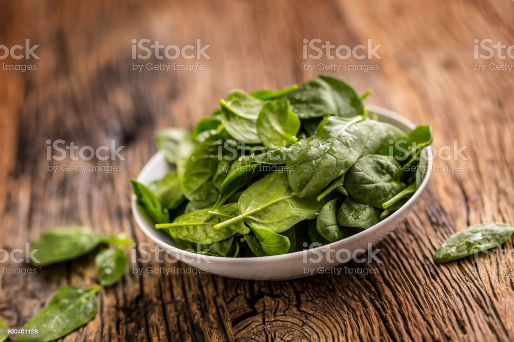 Spinach. Fresh baby spinach leaves in plate on woden table stock photo