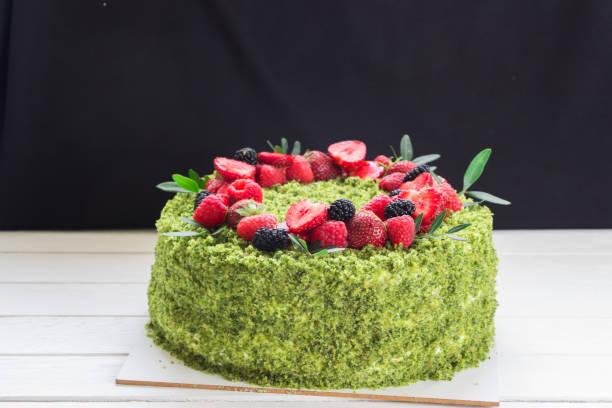 spinat grüner kuchen mit kranz aus frischen beeren. grüner kuchen, grüner keks, erdbeere, himbeere, weißes brett - grüntee kuchen stock-fotos und bilder