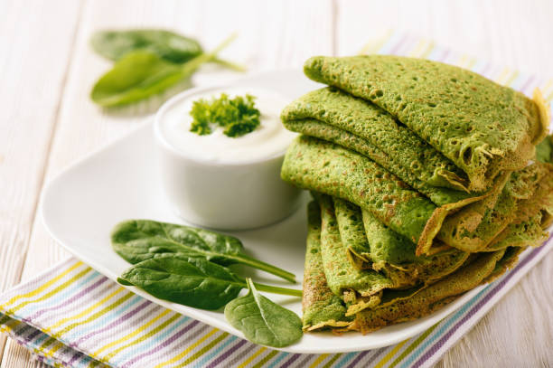 Spinach green pancakes (crepes) with sour cream. stock photo