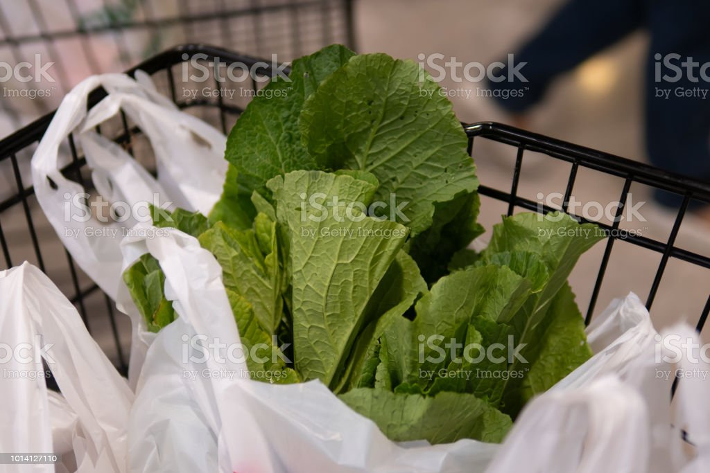 Spinach in plastic bag in shopping cart stock photo