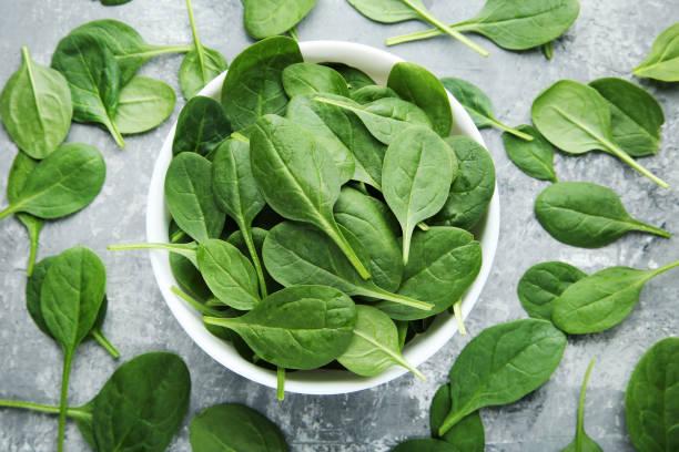 spinach leafs in bowl on grey wooden table - szpinak zdjęcia i obrazy z banku zdjęć