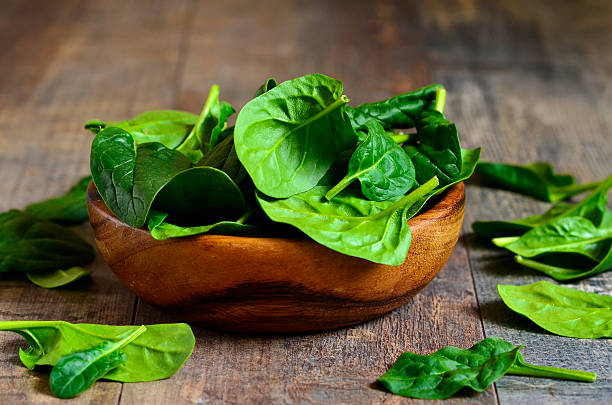 Spinach leaves in a wooden bowl. stock photo