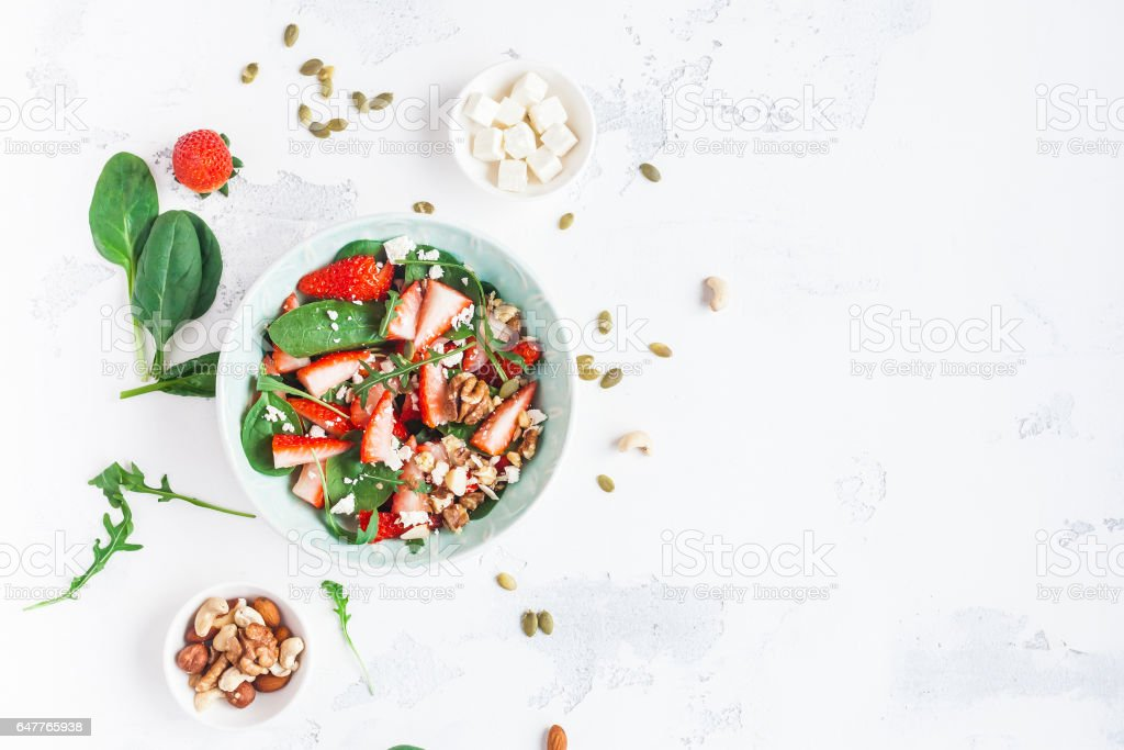 Spinach leaves, sliced strawberries, nuts, feta cheese on white background stock photo